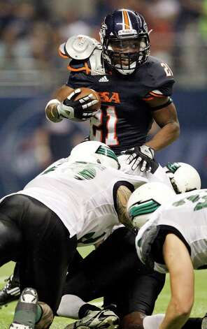 FOR SPORTS - UTSA's Chris Johnson tries to shake the tackle of Northeastern State defenders during first half action Saturday Sept. 3, 2011 at the Alamodome. Photo: EDWARD A. ORNELAS, Express-News / SAN ANTONIO EXPRESS-NEWS (NFS)