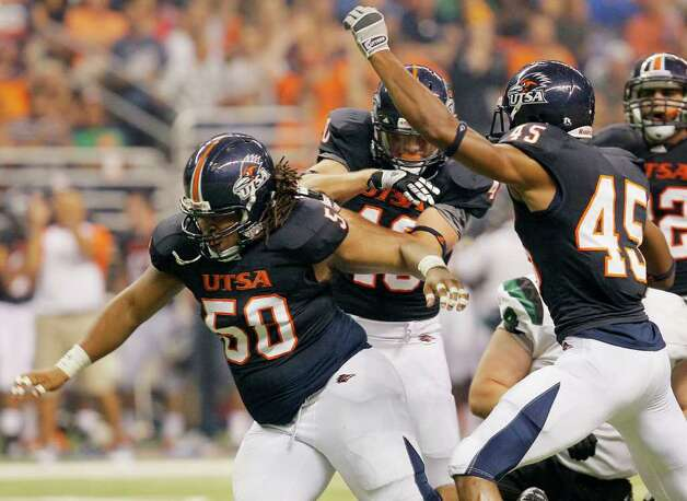 UTSA's Ferrington Macon, left, celebrates a sack with teammates William Ritter, center, and Marlon Smith during the first half of an NCAA college football game against Northeastern State, Saturday, Sept. 3, 2011, at the Alamodome in San Antonio. (AP Photo/Darren Abate) Photo: Express-News