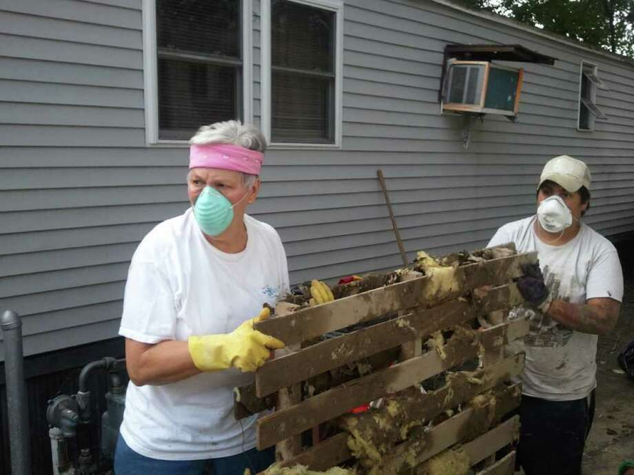 Georgia Holland, a volunteer from Christ Church United Methodist of Troy, and Miriam Santiago, who lives in a trailer home on First Avenue, carry away debris from the home from the flooding of Tropical Storm Irene. Sept. 3, 2011. (Brian Nearing/Times Union)