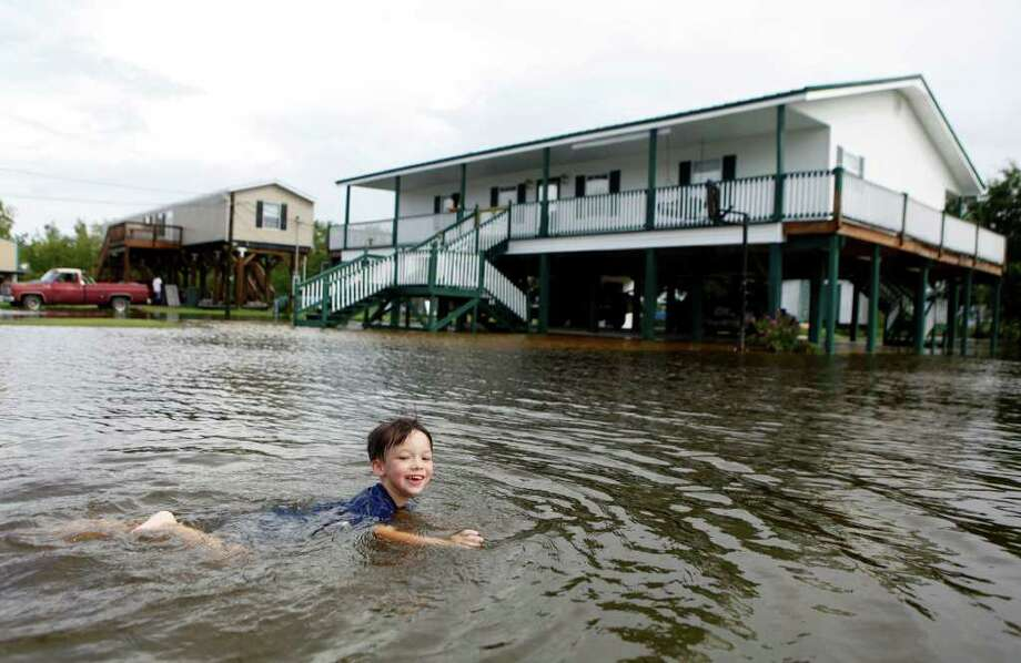 Reuben Dardar, 4, plays in the flood water brought by Tropical Storm Lee outside of his home Saturday, Sept. 3, 2011 in Pointe-aux-Chenes, La. Heavy rains from Tropical Storm Lee were falling in southern Louisiana and pelting the Gulf Coast on Saturday as the storm's center trudged slowly toward land. Photo: Julia Rendleman, Associated Press / Houma Courier