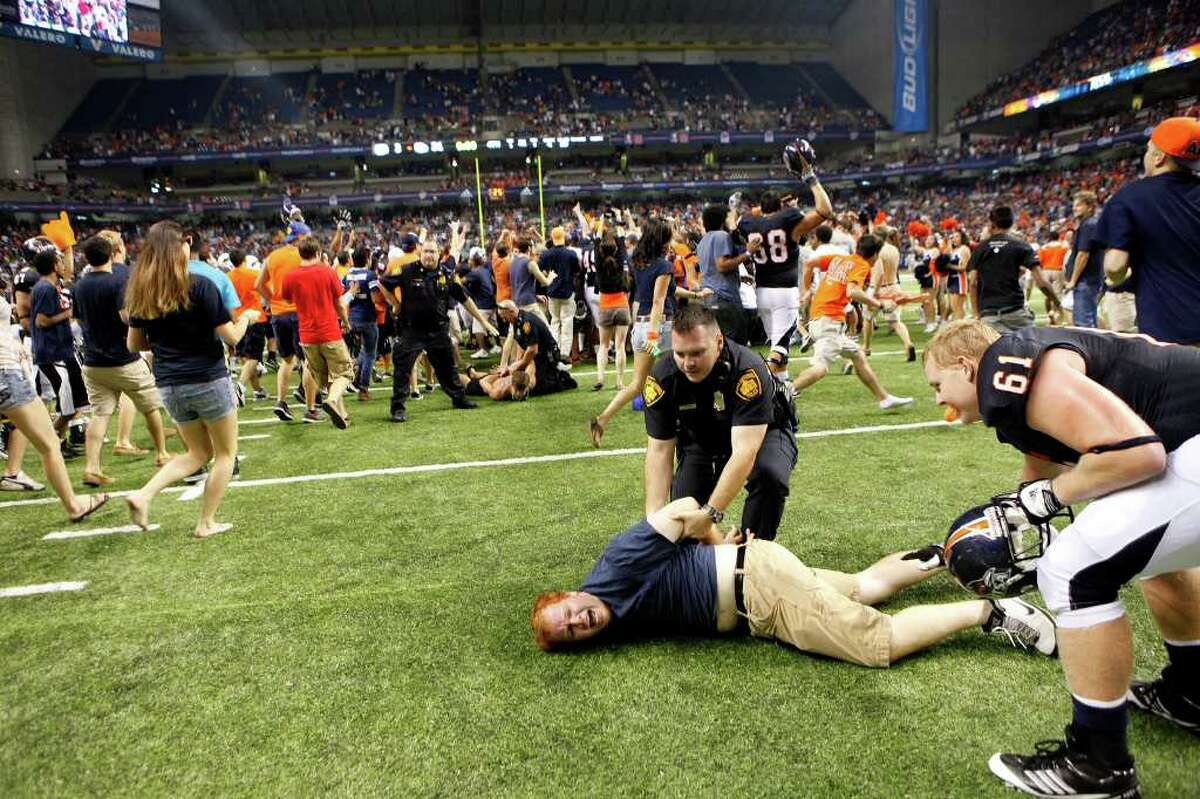Fans are arrested as more rush the field at the conclusion of UTSA's inaugural football game against Northeastern State at the Alamodome on Saturday, Sept. 3, 2011. LISA KRANTZ/lkrantz@express-news.net
