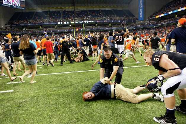 Fans are arrested as more rush the field at the conclusion of UTSA's inaugural football game against Northeastern State at the Alamodome on Saturday, Sept. 3, 2011. LISA KRANTZ/lkrantz@express-news.net Photo: LISA KRANTZ, Express-News / SAN ANTONIO EXPRESS-NEWS