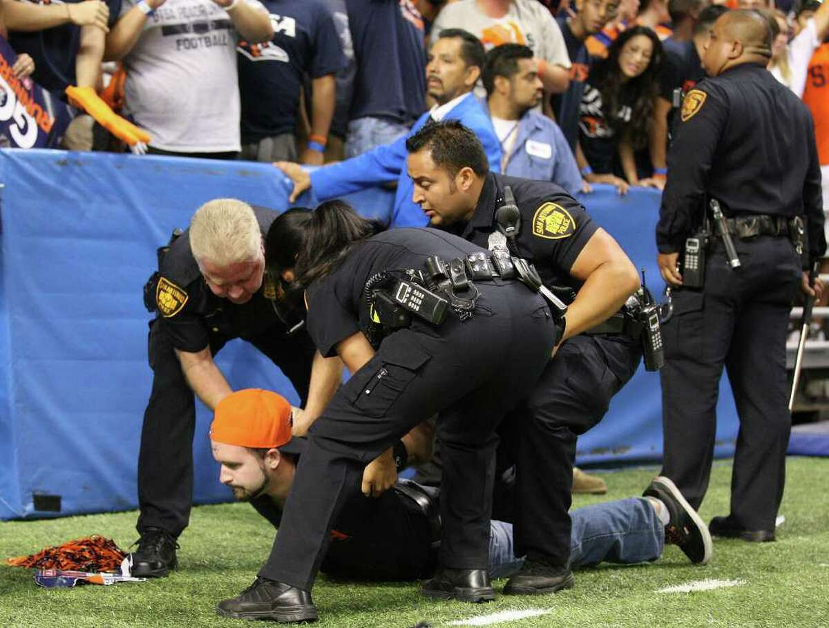 Members of the SAPD detain a UTSA fan after he ran onto the field after the game with Northeastern State Saturday Sept. 3, 2011 at the Alamodome. UTSA won 31-3.