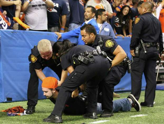 Members of the SAPD detain a UTSA fan after he ran onto the field after the game with Northeastern State Saturday Sept. 3, 2011 at the Alamodome. UTSA won 31-3. Photo: EDWARD A. ORNELAS, Express-News / SAN ANTONIO EXPRESS-NEWS (NFS)