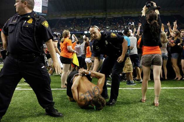 A fan is detained as more rush the field at the conclusion of UTSA's inaugural football game against Northeastern State at the Alamodome on Saturday, Sept. 3, 2011. LISA KRANTZ/lkrantz@express-news.net Photo: LISA KRANTZ, Express-News / SAN ANTONIO EXPRESS-NEWS