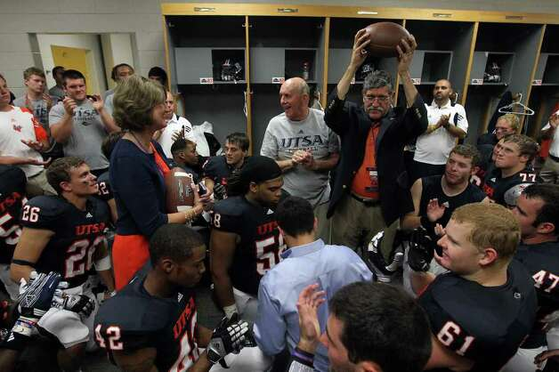 UTSA President Ricardo Romo (right) holds up a game ball presented to him by Head Coach Larry Coker (center) in the team locker room after the Roadrunners won their first inaugural football game against Northeastern State at the Alamodome on Saturday, Sept. 3, 2011. Athletic Director Lynn Hickey was also presented a game ball. UTSA defeated Northeastern State, 31-3. Kin Man Hui/kmhui@express-news.net Photo: Kin Man Hui, Express-News / SAN ANTONIO EXPRESS-NEWS (NFS)