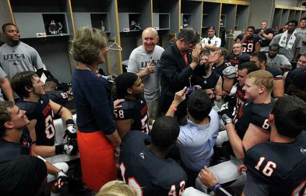 UTSA's head coach Larry Coker (center) gestures after congratulating his team for winning their first football game against Northeastern State as Athletic Director Lynn Hickey (left) and UTSA President Ricardo Romo (right) join in the celebration in the team locker room at the Alamodome on Saturday, Sept. 3, 2011. UTSA defeated Northeastern State, 31-3. Kin Man Hui/kmhui@express-news.net Photo: Kin Man Hui, Express-News / SAN ANTONIO EXPRESS-NEWS (NFS)