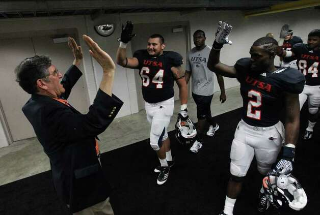 UTSA president Ricardo Romo (left) offers high-fives to players Franky Anaya (64) and Jeremy Hall (2) after the Roadrunners won their inaugural football game against Northeastern State, 31-3, at the Alamodome on Saturday, Sept. 3, 2011. Kin Man Hui/kmhui@express-news.net Photo: Kin Man Hui, Express-News / SAN ANTONIO EXPRESS-NEWS (NFS)