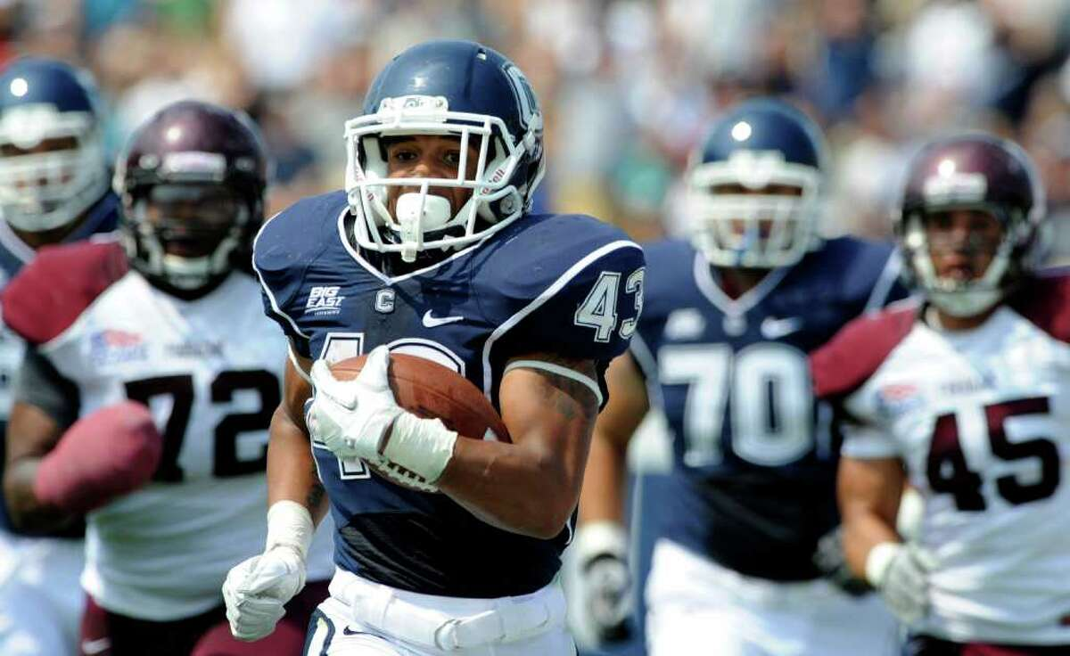 UConn's's Lyle McCombs is pursued by Fordham's Justin Yancey (72) and Jake Rodriques (45) while making a 60-yard run during the first half Saturday in East Hartford, Conn.