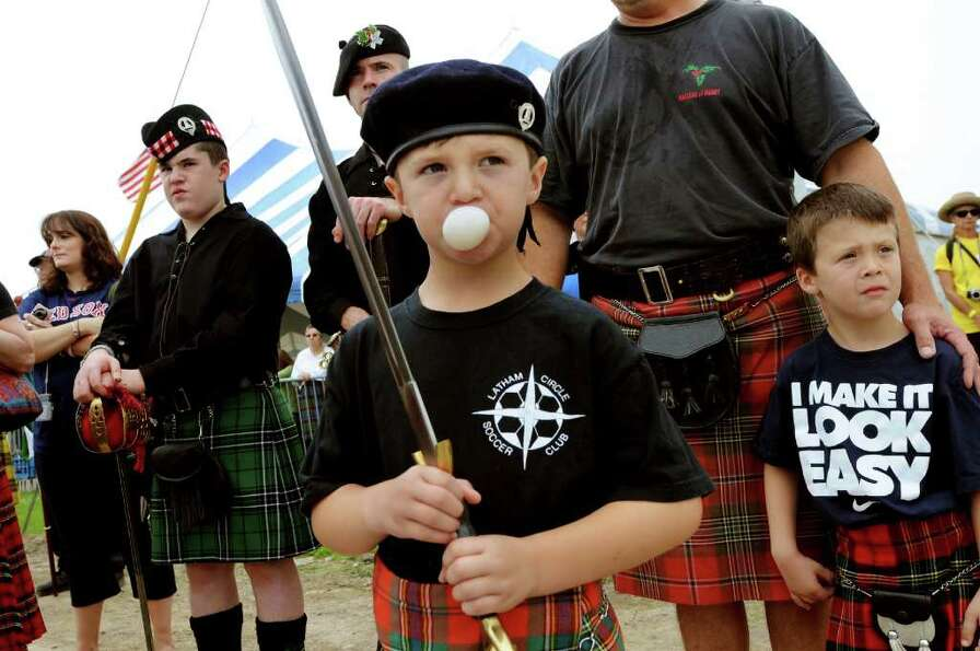 Ben Montimurro, 6, of Latham, center, blows a bubble while he represents the Maclean Clan with his f