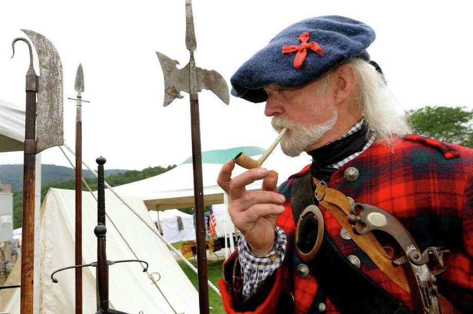 Re-enactor Ken Grant of Eliot, Maine, who's dressed as a 1730's Highland Independent Company man, lights an authentic pipe during the Scottish Games on Saturday, Sept. 3, 2011, at Altamont Fairgrounds in Altamont, N.Y. (Cindy Schultz / Times Union) Photo: Cindy Schultz
