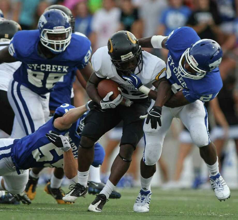 Klein Oak's Larenzo Stewart, center, is tackled by Cy-Creek's Philip Thomas, right, and Daniel Knapp during the first half of Saturday's game at the Berry Center. Photo: Eric Christian Smith, For The Chronicle