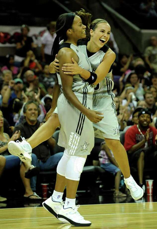 Becky Hammon, right, embraces teammate Jia Perkins of the San Antonio Silver Stars after Perkins scored despite being fouled during WNBA action against the Seattle Storm at the AT&T Center on Saturday, Sept. 3, 2011. BILLY CALZADA / gcalzada@express-news.net