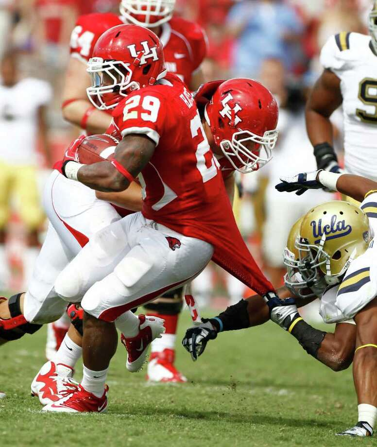Nick de la Torre: Chronicle STRETCH RUN: UH running back Michael Hayes isn't about to let a tug on his jersey stop him on a scintillating  34-yard touchdown run in the second quarter Saturday. Photo: Nick De La Torre, Staff / © 2011 Houston Chronicle