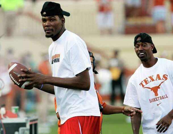 Kevin Durant and TJ Ford get some sideline passes in during the pregame as the Texas Longhorns play the Rice Owls at Darrell K. Royal memorial Stadium on September 3, 2011.  Tom Reel/Staff Photo: TOM REEL, Express-News / © 2011 San Antonio Express-News