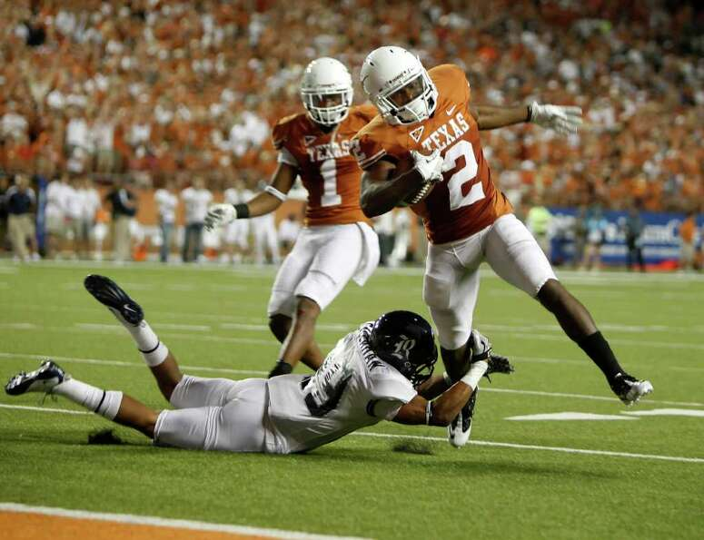 Longhorns running back Fozzy Whittaker (2) runs in a fourth-quarter touchdown past cornerback Bryce