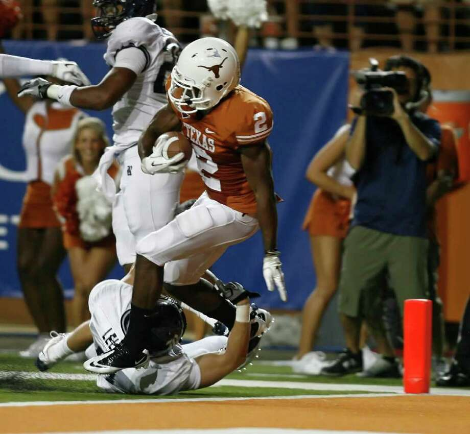 Texas running back Fozzy Whittaker (2) runs over safety Tanner Leland to score his second touchdown in the fourth quarter. Photo: Erich Schlegel, Getty / 2011 Getty Images
