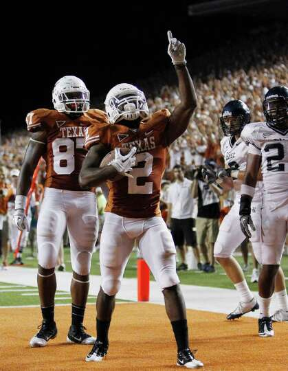 Texas' Fozzy Whittaker (2) celebrates a touchdown during the fourth quarter.