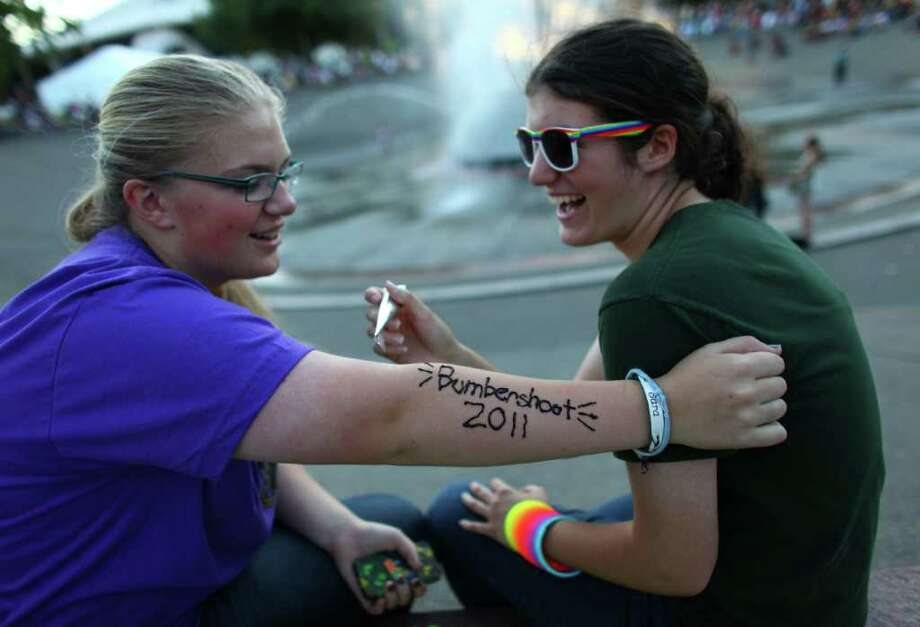 "Kara Alden, 15, uses henna to write ""Bumbershoot 2011"" on the arm of Sara Baumert, 15, during day one of Bumbershoot at Seattle Center on Saturday, Sept. 3, 2011. Photo: JOSHUA TRUJILLO / SEATTLEPI.COM"