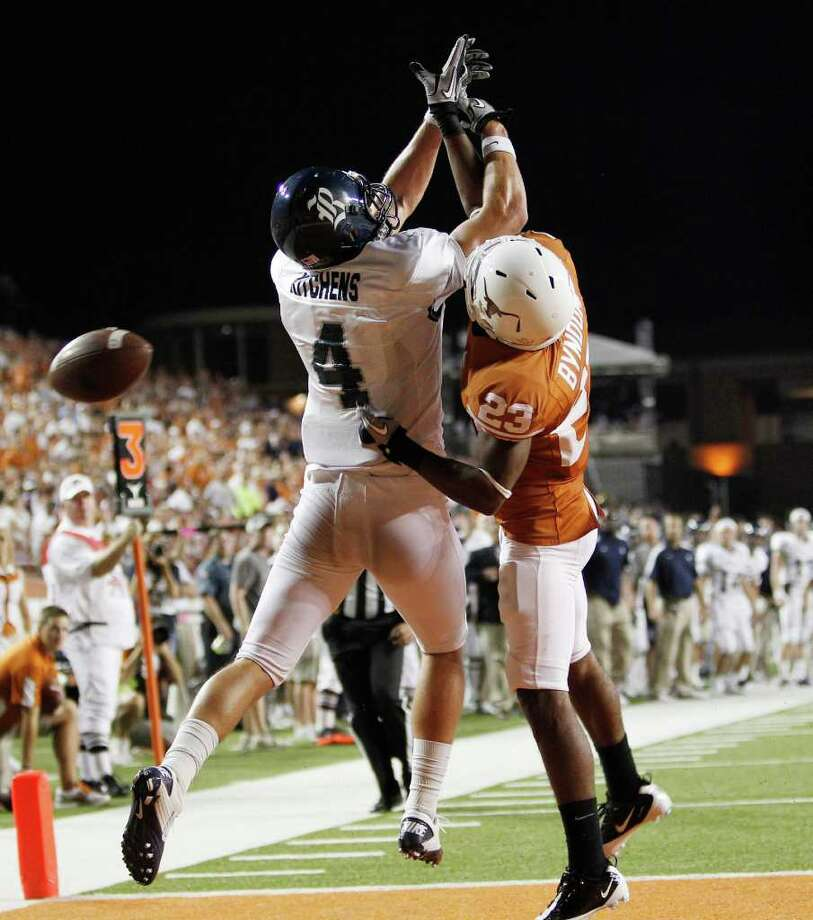 A bid for a touchdown reception by Rice's Randy Kitchens is spoiled by tight coverage from Texas' Carrington Byndom. ( Associated Press) Photo: Eric Gay, STF / AP