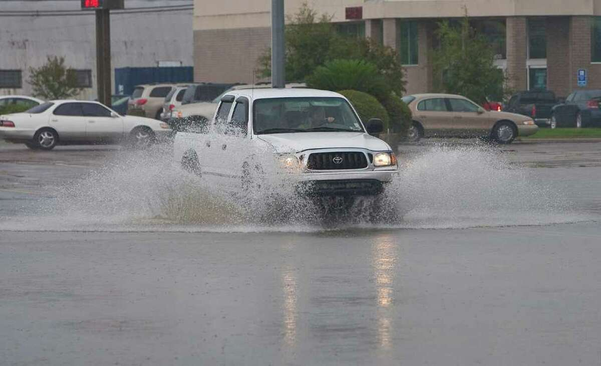 A truck drives through a flooded Market St. in Pascagoula, Miss. as Tropical Storm Lee begins to make landfall on Saturday, Sept. 3, 2011. (AP Photo/Mobile Press-Register, Joshua Dahl)