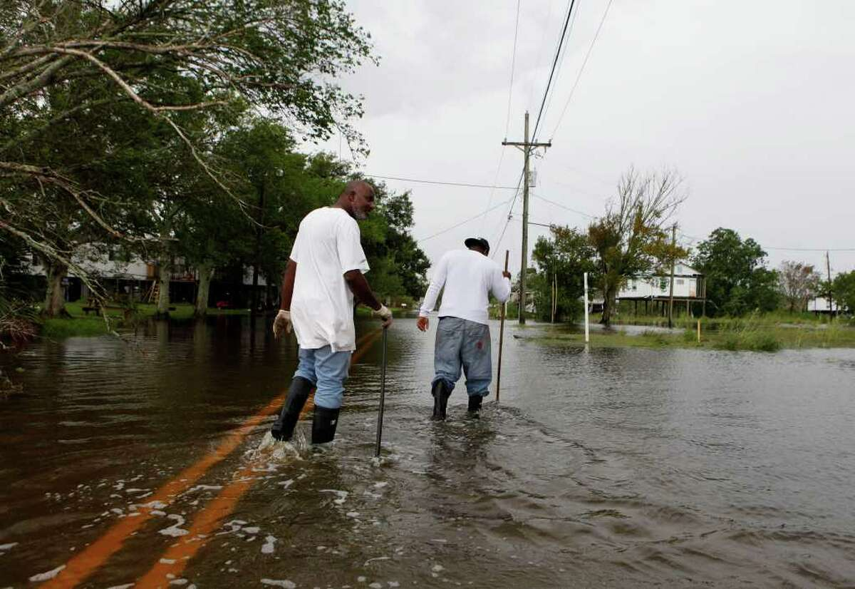 Terrebonne Parish Road and Bridge workers Bernard Johnson, 55, left, and Kodi Smith, 26, both of Houma, La. check for deep pockets of water along Shrimpers Row in Dulac, La. on Saturday, Sept. 3, 2011. (AP Photo/The Houma Daily Courier, Julia Rendleman)