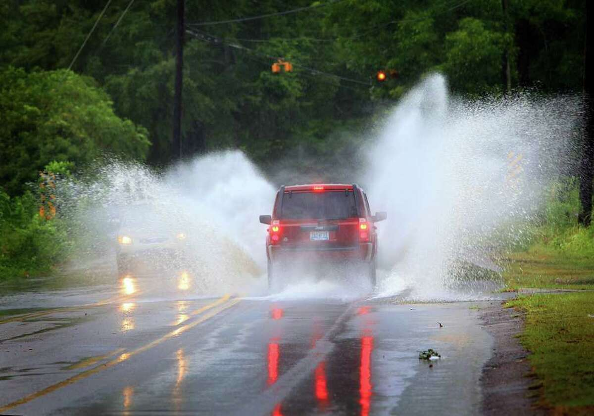Vehicles drive through standing water on McVay Dr. in Mobile, Ala. on Saturday, Sept. 3, 2011. Tropical Storm Lee drenched the area with heavy rains. (AP Photo/Press-Register, Kate Mercer)