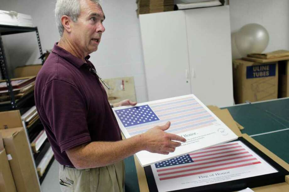 In this Wednesday, Aug. 17, 2011 photo, John Michelotti, founder of the Flag of Honor/Flag of Heroes Project, speaks during an interview in his warehouse in Greenwich, Conn. At first glance, the Flag of Honor/Flag of Heroes Project looks like any other charity doing philanthropy in the name of 9/11. But people who have bought one of its flags would likely be surprised to learn that nearly all the proceeds have gone to the charity founder's for-profit flag company, not 9/11 victims. (AP Photo/Seth Wenig) Photo: Seth Wenig, Associated Press / AP