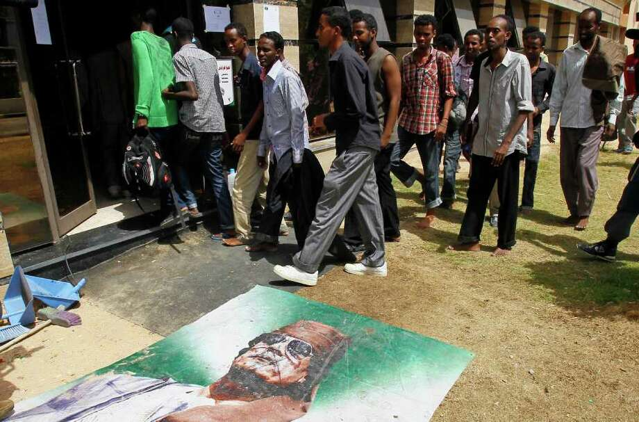 FRANCOIS MORI : ASSOCIATED PRESS DETAINED: A group Somalis suspected of being mercenaries for Moammar Gadhafi walk past his poster in the Tripoli Oil Institute  building in Tripoli, Libya, where they are being held by the rebel Zentan Al Kakaa Brigade. Photo: Francois Mori, STF / AP