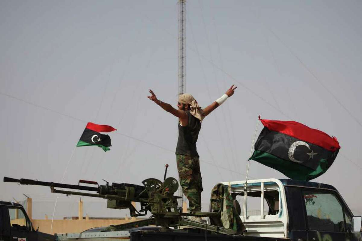 A rebel fighter gestures next to pre-Gadhafi flags at a checkpoint between Tarhouna and Bani Walid, Libya, Sunday, Sept. 4, 2011. Libyan rebels are poised to attack one of Moammar Gadhafi's remaining strongholds, but their military spokesman said Sunday he expected the town's tribal leaders to surrender rather than see their divided followers fight one another. (AP Photo/Alexandre Meneghini)