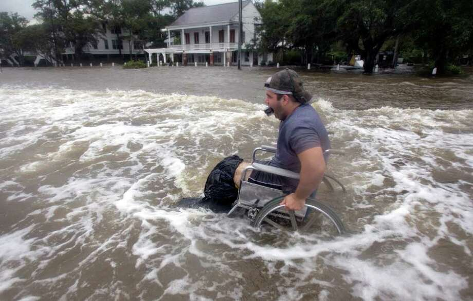 Cecil Flemming tries to maneuver his wheelchair through the waters on the Mandeville, La.  lakefront of Lake Pontchartrain after waters crashed over the seawall from Tropical Storm Lee,  on Sunday, Sept.  4, 2011.  The vast, soggy storm system spent hours during the weekend hovering in the northernmost Gulf of Mexico. Its slow crawl to the north gave more time for its drenching rain bands to pelt a wide swath of vulnerable coastline, raising the flood threat.   (AP Photo/The Times-Picayune, Ted Jackson) Photo: TED JACKSON