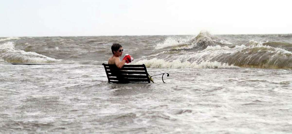 An unidentified man sits on a park bench as waves from Lake Pontchartrain crash over the breakwater from Tropical storm Lee on Sunday, Sept. 4, 2011 at Mandeville, La. The vast, soggy storm system spent hours during the weekend hovering in the northernmost Gulf of Mexico. Its slow crawl to the north gave more time for its drenching rain bands to pelt a wide swath of vulnerable coastline, raising the flood threat. (AP Photo/The Times-Picayune, Grant Therkildsen)