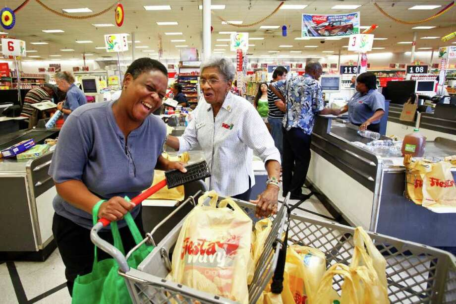 """Mary Bell Balls, 89, right, tells Angela Lewis to """"have a blessed day,"""" after sacking her groceries recently at the Fiesta Mart at Wheeler and San Jacinto. """"I love them all,"""" she says about the customers. Photo: Michael Paulsen, Staff / © 2011 Houston Chronicle"""
