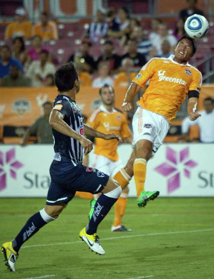 Dynamo forward Brian Ching goes up for a header against CF Monterrey midfielder Miguel Morales during the first half. Photo: Smiley N. Pool, Houston Chronicle / © 2011  Houston Chronicle