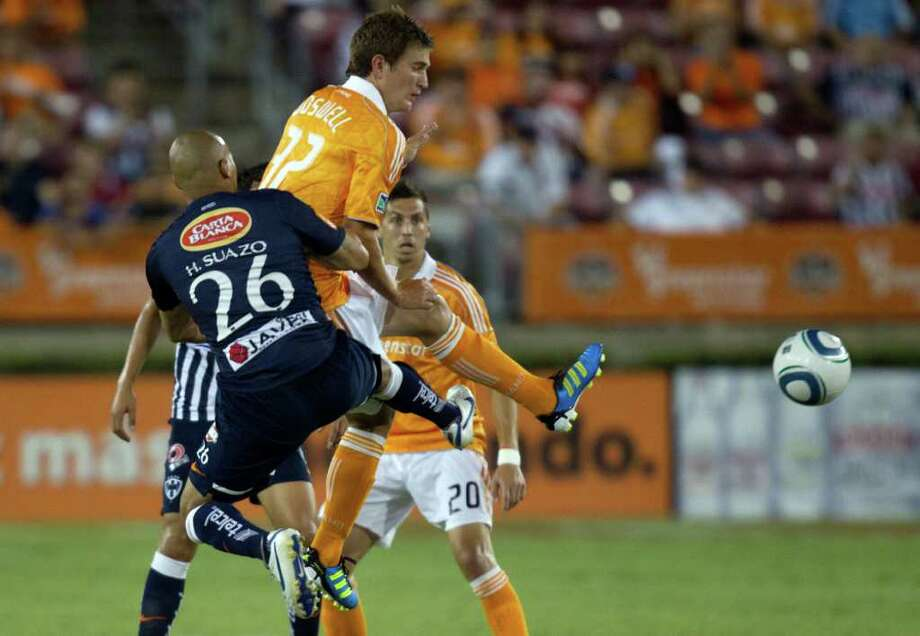 Dynamo defender Bobby Boswell (32) tangles with CF Monterrey forward Humberto Suazo (26) during the first half. Photo: Smiley N. Pool, Houston Chronicle / © 2011  Houston Chronicle