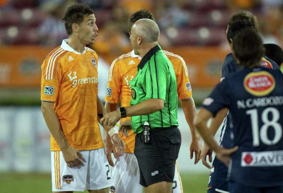 Dynamo defender Geoff Camerson, left, has words with referee Jasen Anno after a penalty call against CF Monterrey during the first half. Photo: Smiley N. Pool, Houston Chronicle / © 2011  Houston Chronicle