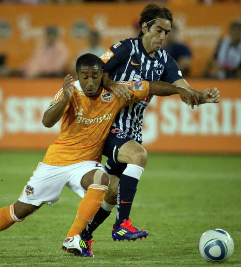 Dynamo defender Corey Ashe, left, is challenged by  CF Monterrey midfielder Cesar Delgado. Photo: Smiley N. Pool, Houston Chronicle / © 2011  Houston Chronicle