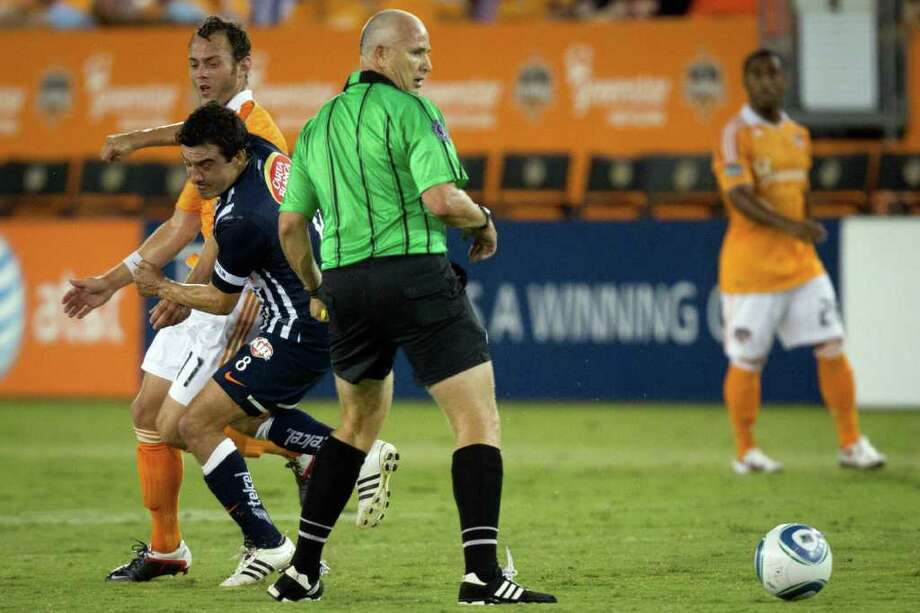 Dynamo midfielder Brad Davis, rear, gets an elbow from CF Monterrey midfielder Luis Ernesto Perez that resulted in Perez being sent off by referee Jasen Anno, center, during the first half. Photo: Smiley N. Pool, Houston Chronicle / © 2011  Houston Chronicle