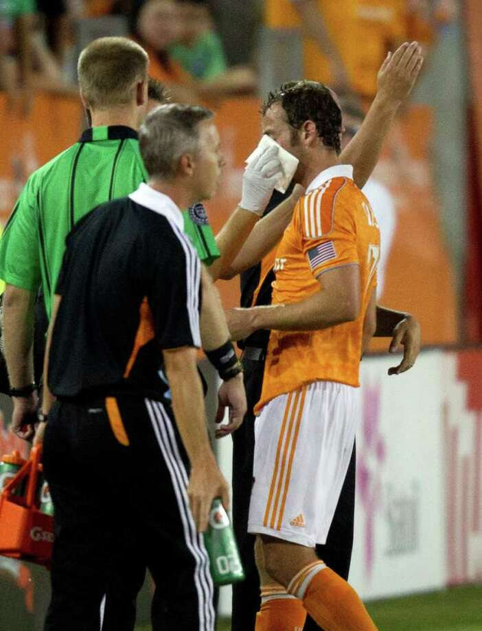 Dynamo midfielder Brad Davis, right, receives medical attention after taking an elbow from CF Monterrey midfielder Luis Ernesto Perez, who was sent off during the first half. Photo: Smiley N. Pool, Houston Chronicle / © 2011  Houston Chronicle