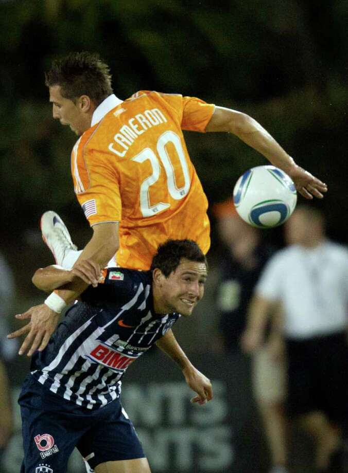 Dynamo defender Geoff Cameron (20) collides with CF Monterrey forward Dario Carreno while challenging for a header during the first half. Photo: Smiley N. Pool, Houston Chronicle / © 2011  Houston Chronicle