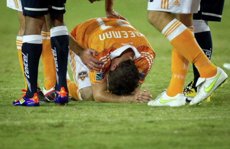 Dynamo defender Hunter Freeman collapses on the ground after a hit that resulted in CF Monterrey forward Humberto Suazo being sent off during the first half. Photo: Smiley N. Pool, Houston Chronicle / © 2011  Houston Chronicle