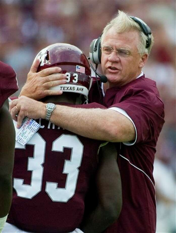 Texas A&M head coach Mike Sherman, right, hugs Christine Michael (33) after he scored a touchdown during the first quarter against SMU,Sept. 4, 2011, in College Station. Photo: DAVE EINSEL, Associated Press / FR43584 AP