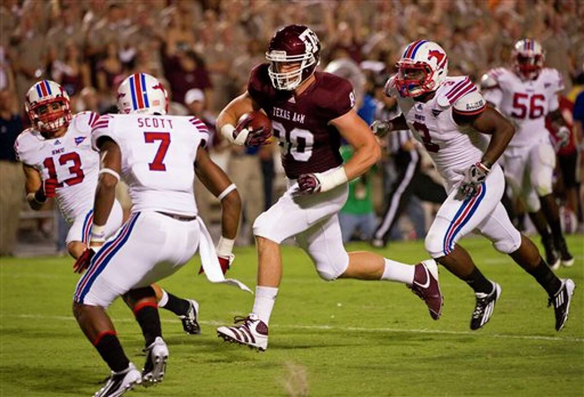 Texas A&M tight end Hudson Prioleau (80) splits SMU defenders Chris Castro (13) Jay Scott (7) and Kevin Pope (3) to score a touchdown during the third quarter of an NCAA college football game, Sunday, Sept. 4, 2011, in College Station, Texas. A&M beat SMU 46-14. (AP Photo/Dave Einsel)