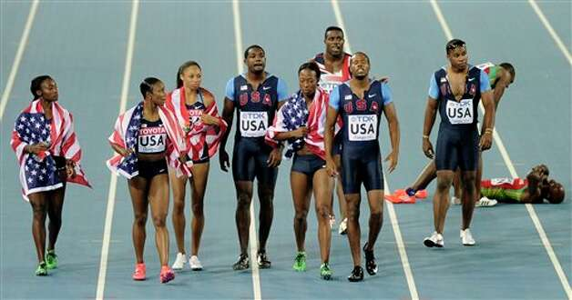 USA's Darvis Patton, seventh from left, is consoled by USA's women's relay team member Marshevet Myers, sixth from left, after he dropped the baton in the Men's 4x100 Relay final at the World Athletics Championships in Daegu, South Korea, Sunday, Sept. 4, 2011. (AP Photo/Martin Meissner) Photo: Martin Meissner, Associated Press / AP