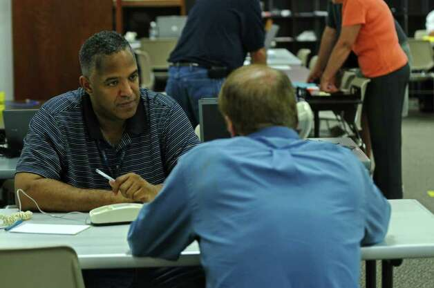"FEMA Disaster Recovery Center Manager Carlos Isales, left, works with Leon Brunez of Scotia, right, a victim of last Sunday's Tropical Storm Irene,  at the FEMA center set up in Rotterdam Square Mall on Sunday Sept. 4, 2011 in Rotterdam, NY.   ""We lost everything,"" said Brunez.(Philip Kamrass / Times Union) Photo: Philip Kamrass / 00014512A"