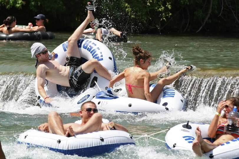 A tuber wipes out going over a dam on the Comal River on Labor Day weekend, Sunday, Sept. 4, 2011. T