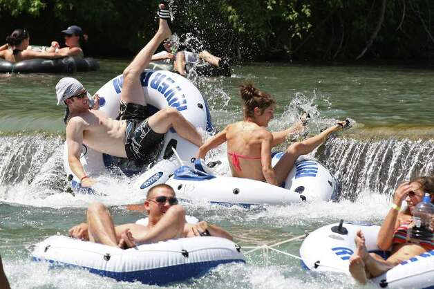 A tuber wipes out going over a dam on the Comal River on Labor Day weekend, Sunday, Sept. 4, 2011. The New Braunfels Police Department beefed up their weekend patrol from a unit of six to over 40 officers to insure public safety on the river. Photo: JERRY LARA, Jerry Lara/Express-News / SAN ANTONIO EXPRESS-NEWS