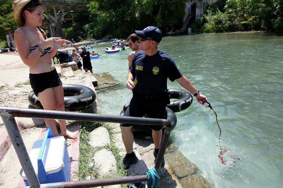 New Braunfels Police Department Officer Michael Smith empties confiscated glass wine bottles while patrolling the Comal River on Labor Day weekend, Sunday, Sept. 4, 2011 in New Braunfels, Texas. New Braunfels recently passed an ordinance banning containers on the parts of the Comal River and Guadalupe River in New Braunfels. The ban goes in to effect Jan. 1, 2012. Photo: Jerry Lara/Express-News