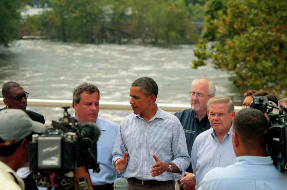 President Barack Obama, center, talks to reporters on the Temple Street Bridge over the Passaic River as he visits areas damaged by Hurricane Irene, Sunday, Sept. 4, 2011, in Paterson, N.J. Gov. Chris Christie stands left of Obama. (AP Photo/John O'Boyle, Pool) Photo: John O'Boyle