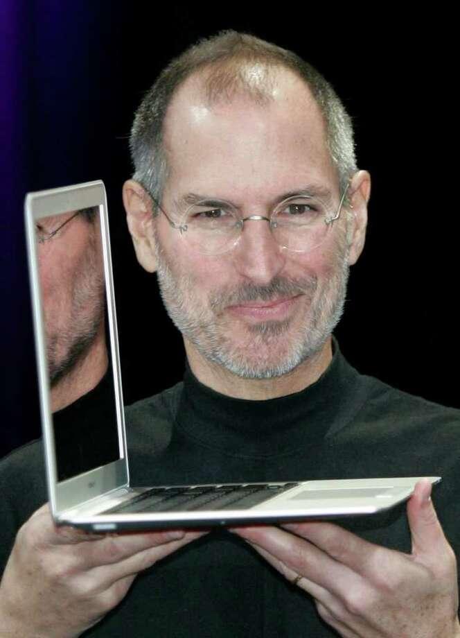 Apple CEO Steve Jobs holds up the MacBook Air after his keynote at the MacWorld Conference in San Francisco, Tuesday, Jan. 15, 2008.  The super-slim new laptop is less than an inch thick and turns on the moment it's opened. (AP Photo/Paul Sakuma) Photo: Paul Sakuma / AP2008